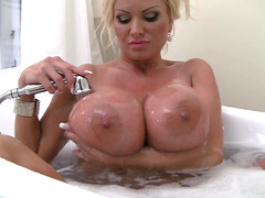 Buxom MILF Sharon Pink lathers her monster juggs in the hot suds of a bubble bath